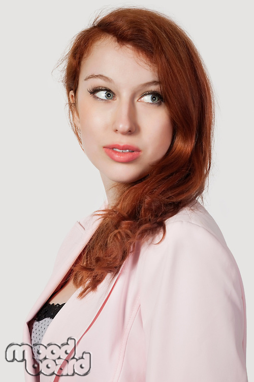 Beautiful young businesswoman in pink suit looking away against gray background