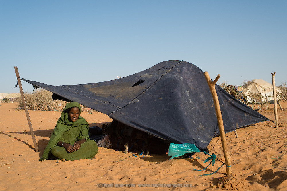 According to her identity card, Oumi Walet Idwale was registered as having arrived in the the Mbera camp for Malian refugees in Mauritania on 14 november 2013. As of 11 March 2013, when this photograph was taken, she and her father had still not received a tent in which to live. According to Oumi they have repeatedly been told that there are no tents available, but that they should keep checking back. Oumi does not know what has happened to her mother - when her village fled Mali in a panic they were separated and she has not seen her mother since.