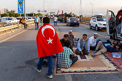 © Licensed to London News Pictures. 17/07/2016. Istanbul, Turkey. Turkish government supporters camp out with Turkish police officers to protect army tanks left outside Istanbul's Sabiha Gokcen airport following a failed coup attempt by groups in Turkish military on 15 July 2015. Many tourists whose flights were delayed or cancelled following Friday's coup attempt try to get new flights on Sunday, 17 June 2016. Photo credit: Tolga Akmen/LNP