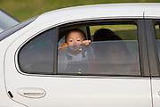 Jeju Island. Toursit kid in rental car.