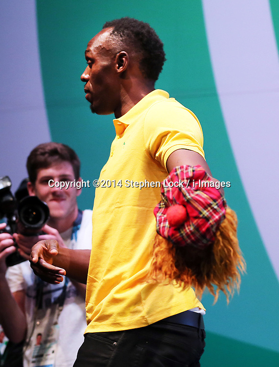Image licensed to i-Images Picture Agency. 26/07/2014. Glasgow, United Kingdom. Usain Bolt  is given a Scottish Jimmy hat at the end  of a press conference on day three of the Commonwealth Games in Glasgow where he confirmed his attendance in the Relay event at the Games.  Picture by Stephen Lock / i-Images