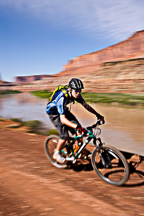 Mountain biker Wyatt Johnson (age 15) rides along the Green River on the White Rim Trail in Canyonlands National Park, Utah.