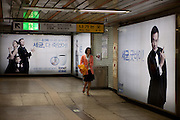Junge Frau in einer Station der Metro in Seoul mit dem Ausgang zur Korean Development Bank.  <br /> <br /> Young woman at a Seoul Metro station with the exit to the Korean Development Bank.