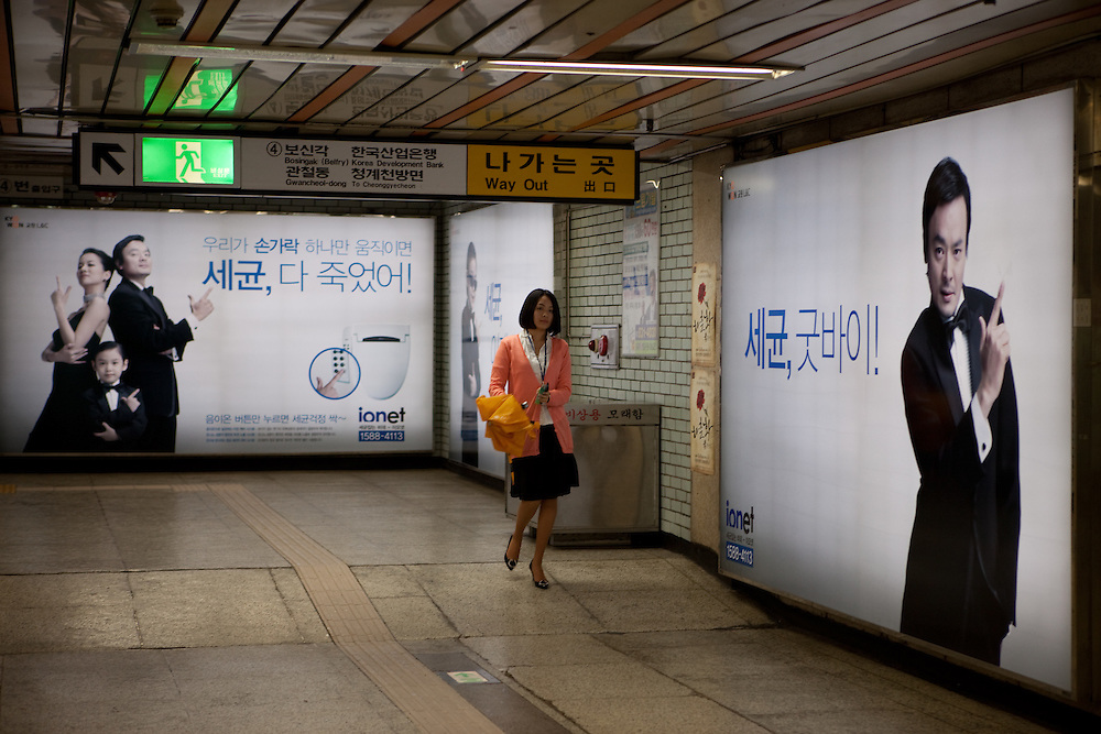 Junge Frau in einer Station der Metro in Seoul mit dem Ausgang zur Korean Development Bank.  <br /> <br /> Young woman at a Seoul Metro station with the exit to the Korean Development Bank.