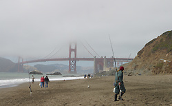 Summer fog covers the top of the Golden Gate Bridge, while staying above the beach, in San Francisco, California.