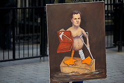 © licensed to London News Pictures. London, UK 18/03/2015. Artist Kaya Mar holding an illustration of Chancellor of the Exchequer George Osborne outside Downing Street on the Budget Day, Wednesday, 18 March 2015. Photo credit: Tolga Akmen/LNP
