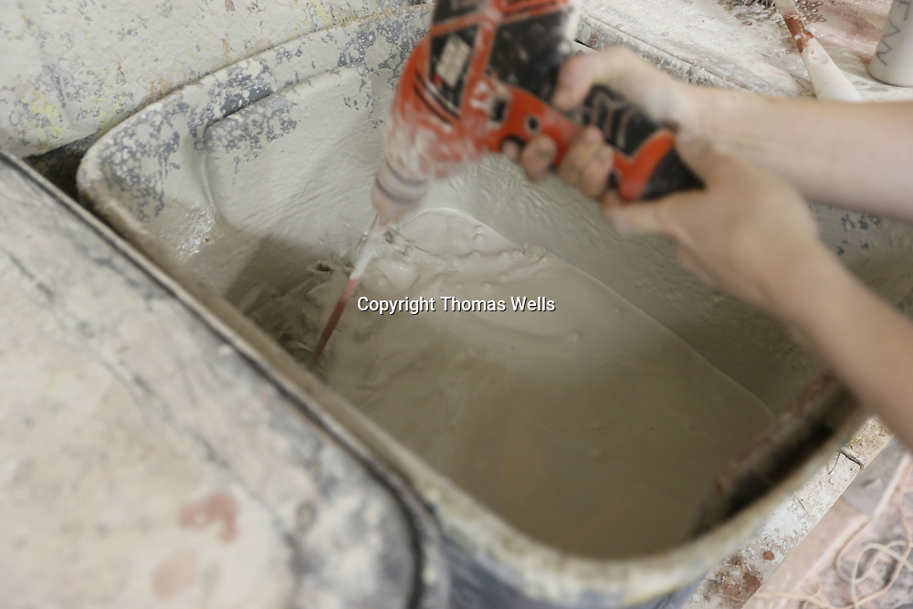 """A power drill with a mixer attached is used to stir up the underglaze before they can begin applying the """"ocean"""" glaze."""