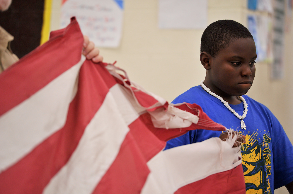 Boy Scout Troop 772's Deshawn Mills participates in an American flag-folding lesson by Assistant Scoutmaster Donald Lucy at Dan McCarty Middle School in Fort Pierce on April 16, 2014.