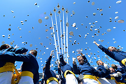 Cadets throw their hats in the air as the Air Force Thunderbirds fly over the United States Air Force Academy 58th graduation commencement at Falcon Stadium.