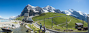 """Walk downhill from Eigergletscher train station (of the Jungfraujoch """"Top of Europe"""" railway) under the north face of the Eiger (3970m / 13,020 ft elevation) to Alpiglen station in Grindelwald Valley, Canton of Bern, Switzerland, the Alps, Europe. The Eiger has the biggest north face in the Alps: 1800 vertical meters (or 5900 ft) of rock and ice. The Swiss Alps Jungfrau-Aletsch region is honored as a UNESCO World Heritage Site.The Swiss Alps Jungfrau-Aletsch region is honored as a UNESCO World Heritage Site. This image was stitched from multiple overlapping photos."""