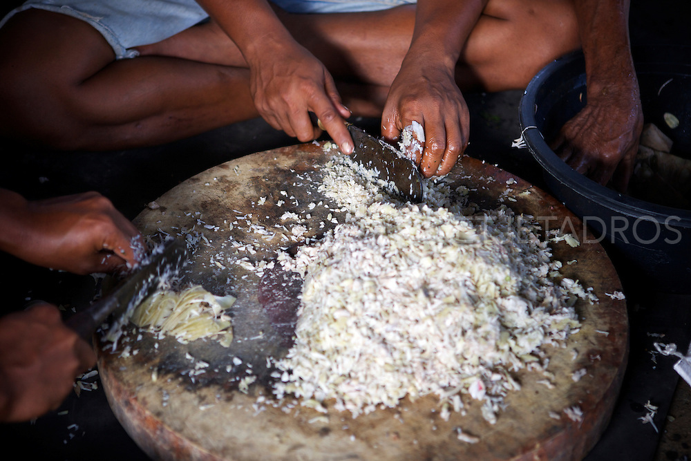 Men chopping pork and rice in preparation for a Balinese wedding<br />