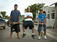 three boys pose in Culebra with a homemade tricycle