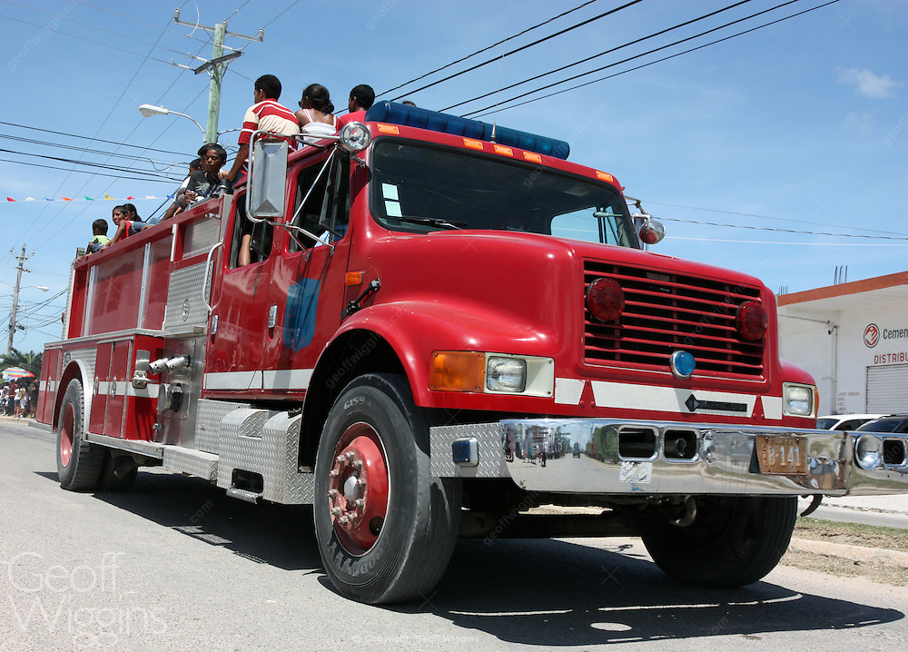 New Belize fire truck carrying children in carnival. A gift from the USA