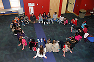 Outdoor facilitator John Betts of Vandalia (sitting under white fire extinguisher box) talks safety  to Girl Scouts before they go outside during Program Aide (PA) training at the Girl Scouts Urban Campus in Dayton, Saturday, March 3, 2012.