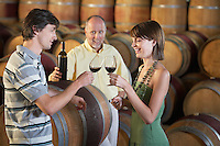 Three people wine-tasting beside wine casks