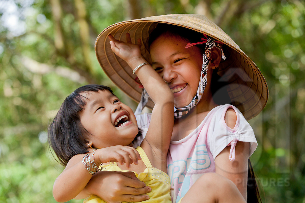 Young child smiling and laughing in the arms of another happy girl wearing a conical hat, Tay Ninh Province, Vietnam, Southeast Asia