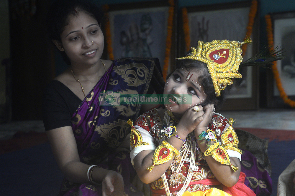 August 14, 2017 - Kolkata, West Bengal, India - Indian mother finishes make up her child in Lord Krishna attire before participate in Janmastami festival in Kolkata. Children dress up like Lord Krishna to participate the Janmastami festival at the temple on August 14, 2017 in Kolkata. (Credit Image: © Saikat Paul/Pacific Press via ZUMA Wire)