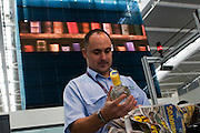 A male security operative uncovers forbidden bottle of Vodka among a passenger's hand baggage during search at Heathrow T5