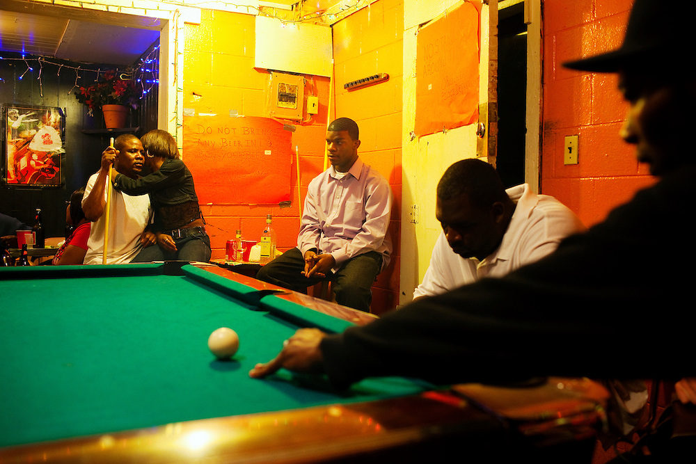 Men and women play pool at Odessa Nicks' one-room club in the Baptist Town neighborhood of Greenwood, Mississippi on February 18, 2011.