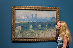 "© Licensed to London News Pictures. 04/08/2020. LONDON, UK. A staff member poses with ""Waterloo Bridge, Overcast"", 1903, by Claude Monet. Preview of ""Gauguin and the Impressionists : Masterpieces from the Ordrupgaard Collection"" at the Royal Academy of Arts in Piccadilly.  60 works from a collection of Impressionist paintings, assembled by wealthy Danish couple Wilhelm and Henny Hansen, are on show 7 August to 18 October 2020, and includes masterpieces by Gauguin, Degas, Monet, Morisot, Pissarro, Renoir and Sisley.  Photo credit: Stephen Chung/LNP"