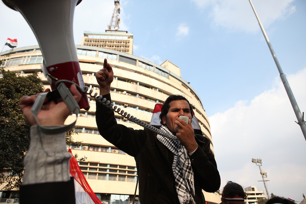 Pro-democracy protesters chant against the Mubarak regime outside the State TV building near Tahrir Square.