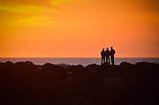 Silhouette of three male friends standing on a rocky shore enjoying the orange sunset over the ocean.