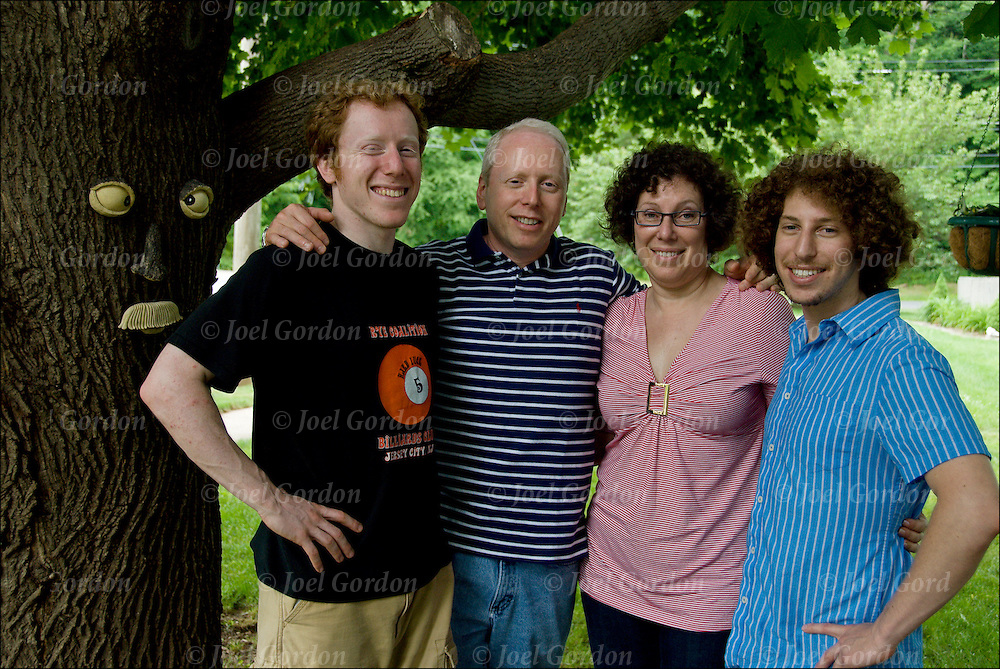 Caucasian family three quarter length portrait outdoors by tree with face. Couple with two young adult sons in their twenties.