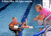 Active Aging Senior Citizens, Retired, Activities, Grandfather helps Granddaughter Swim, Child Learns to Swim, Grandchild Mother and Grandfather