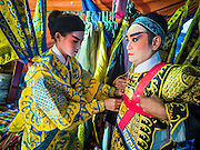 "14 MAY 2015 - BANGKOK, THAILAND:  Chinese opera performers put on their costumes before a show at the Pek Leng Keng Mangkorn Khiew Shrine in the Khlong Toey slum in Bangkok. Chinese opera was once very popular in Thailand, where it is called ""Ngiew."" It is usually performed in the Teochew language. Millions of Chinese emigrated to Thailand (then Siam) in the 18th and 19th centuries and brought their culture with them. Recently the popularity of ngiew has faded as people turn to performances of opera on DVD or movies. There are still as many 30 Chinese opera troupes left in Bangkok and its environs. They are especially busy during Chinese New Year and Chinese holiday when they travel from Chinese temple to Chinese temple performing on stages they put up in streets near the temple, sometimes sleeping on hammocks they sling under their stage. Most of the Chinese operas from Bangkok travel to Malaysia for Ghost Month, leaving just a few to perform in Bangkok.      PHOTO BY JACK KURTZ"