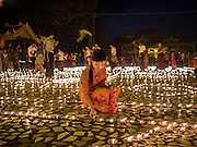 28 OCTOBER 2015 - YANGON, MYANMAR:     A woman lights oil lamps during observances of Thadingyut at Botataung Pagoda in Yangon. Botataung Pagoda was first built by the Mon, a Burmese ethnic minority, around the same time as was Shwedagon Pagoda, over 2500 years ago. The Thadingyut Festival, the Lighting Festival of Myanmar, is held on the full moon day of the Burmese Lunar month of Thadingyut. As a custom, it is held at the end of the Buddhist lent (Vassa). The Thadingyut festival is the celebration to welcome the Buddha's descent from heaven.     PHOTO BY JACK KURTZ