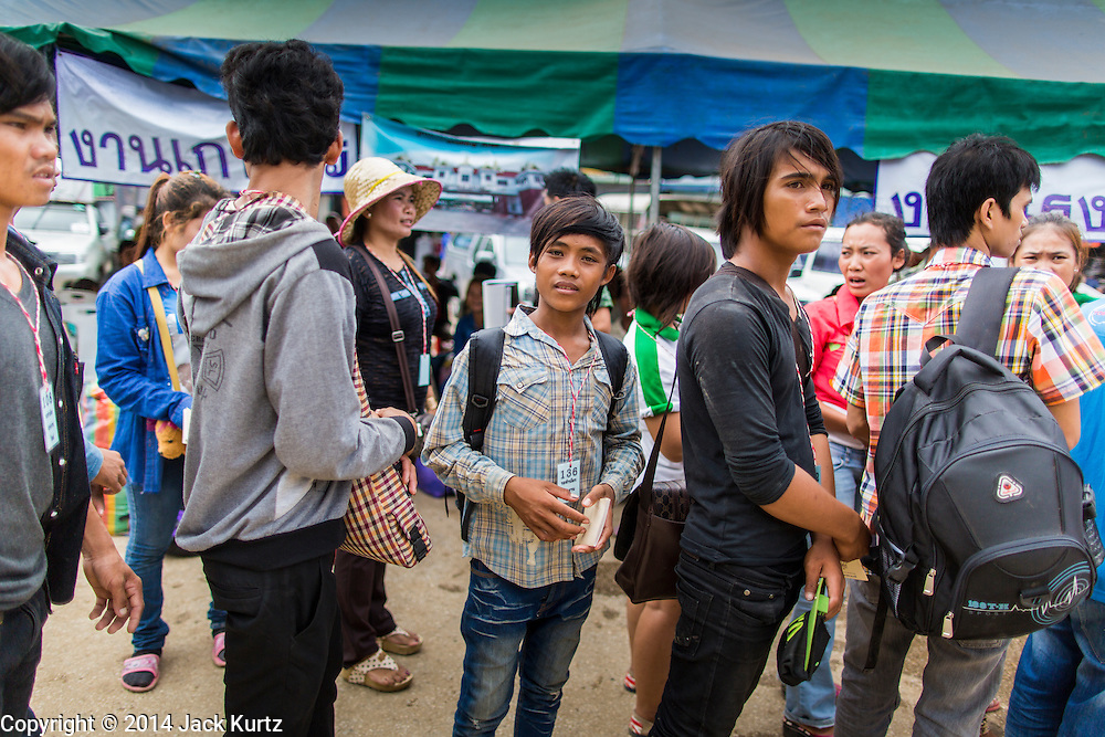 09 JULY 2014 - ARANYAPRATHET, SA KAEO, THAILAND: Cambodian migrant workers line up before going into the Thai Immigration One Stop Service Center in Aranyaprathet on the Thai-Cambodian border. More than 200,000 Cambodian migrant workers, most undocumented, fled Thailand in early June fearing a crackdown by Thai authorities after a coup unseated the elected government. Employers have been unable to fill the vacancies created by the Cambodian exodus and the Thai government has allowed them to return. The Cambodian workers have to have a job and their employers have to vouch for them. The Thai government is issuing temporary ID cards to allow them to travel openly to their jobs. About 800 Cambodian workers came back to Thailand through the Aranyaprathet border crossing Wednesday. The Thai government has opening similar service centers at three other crossing points on the Thai-Cambodian border.    PHOTO BY JACK KURTZ