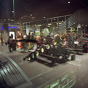 Seen through a glass screen, we see a crowd of passengers - a mixture of business and holiday travellers - awaiting the departure of their commercial flight from Frankfurt am Main international airport, Germany. Reflected lights and other windows merge into this scene of European air travel where the everyday misery of delays and disruption affect millions on a daily basis. Some people are still seated while the more enthusiastic wait in line, queuing for the imminent departure. Frankfurt is also a sprawling hub for the German state airline Lufthansa. Picture from the 'Plane Pictures' project, a celebration of aviation aesthetics and flying culture, 100 years after the Wright brothers first 12 seconds/120 feet powered flight at Kitty Hawk,1903. .
