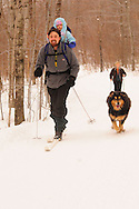 A father carries his baby in a backpack while cross-country skiing with his wife and dog.   Watson's Wonder Trail, Smugglers' Notch, Vermont.