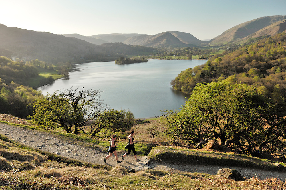 Joggers jogging running on Loughrigg Fell above Grasmere valley and lake in the Lake District National Park, Cumbria, England.