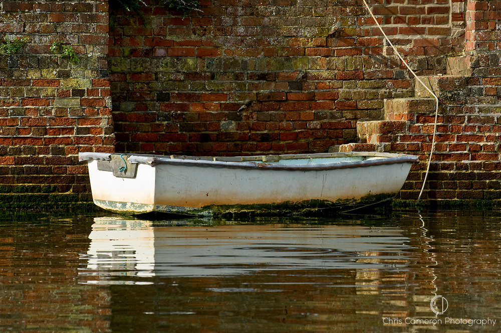 A dinghy tied to a brick wall with stairs to the shore of the Hamble River, Hampshire, England 12/9/2008