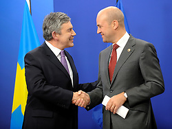 Gordon Brown, the U.K.'s prime minister, left, is greeted by Fredrik Reinfeldt, Sweden's prime minister and standing president of the European Council, as he arrives for the European Summit at the EU headquarters in Brussels, Belgium, on Thursday, Sept. 17, 2009. European Union leaders may call for sanctions on banks that pay excessive bonuses, fearing that runaway executive pay could trigger another financial crisis, a draft text showed. (Photo © Jock Fistick) *** Local Caption *** Gordon Grown