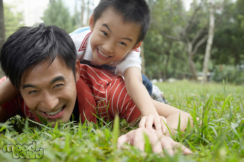 Father and son (7-9) in park lying in grass and laughing