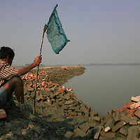 Sitting with his net, this fisherman punctuates a landscape of displaced bricks and water that seems to weave endlessly into the distance.