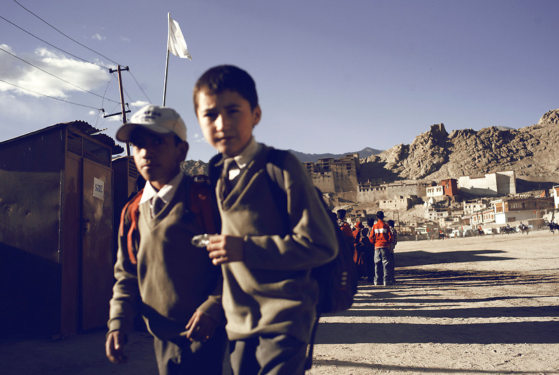 Two boys walk home from school across the playing field after the final of the Ladakh festival polo match in Leh, Ladakh, India on Sep. 13, 2007.