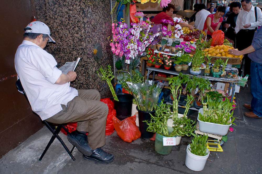An Asian vendor sits and reads the paper on the sidewalk in China Town, NYC.