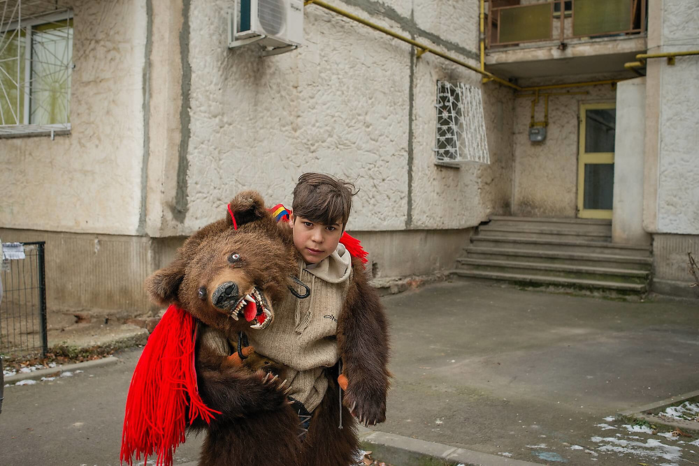 A boy wearing a real bear skin and mask walks with a group of 20 people in Piata Sudului, in south Bucharest. The group came from the rural Bacau area (300 km away from Bucharest), to perform the 'Bear Dance', an ancient ritual that symbolises the death and the rebirth of the bear.