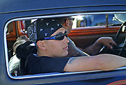 A young attractive man witha bandana and sunglasses riding in a Hotrod car, Viva Las Vegas Festival, Las Vegas, USA 2006.