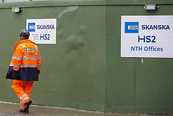 London, UK. 22 January, 2020. A construction worker passes a site designated for the HS2 high-speed rail line close to Euston station. There has been considerable land purchase and clearance in the Euston area. Cost projections for the project are reported to have risen to £106bn and the Transport Secretary Grant Shapps has confirmed that the Government will make a decision regarding its viability in February 2020.