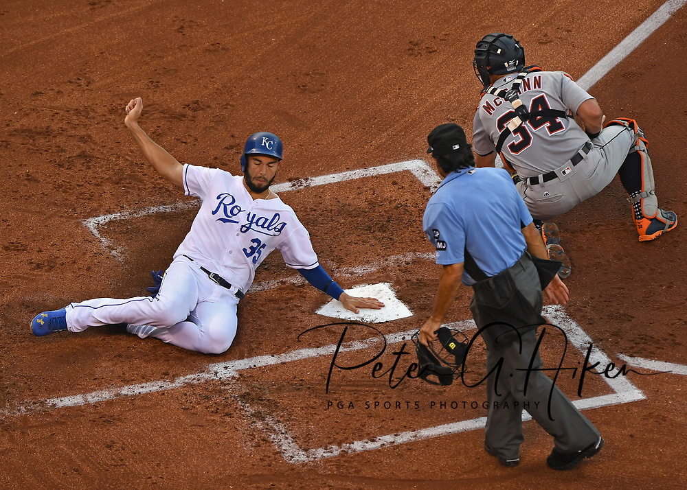 Kansas City Royals base runner Eric Hosmer (35) slides home with a run past Detroit Tigers catcher James McCann (34) during the first inning at Kauffman Stadium.