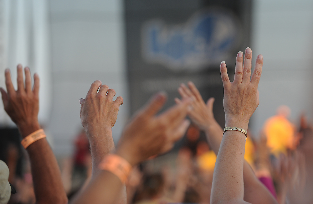 Music fans attending Lifest, a Christian music festival in Oshkosh, Wis., raise their hands during a religious hymn. (Sam Lucero photo)