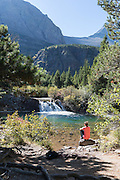 A young woman sits and relaxes enjoying the view of a waterfall along the Swiftcurrent Pass Trail in Glacier National Park, Montana.