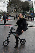 A young woman site on her CleveYoung cBike while using her phone in the street, on 4th February 2017 in London, United Kingdom. The 40lb CleveYoung cBike is a remodeled foldable electric scooter with a Samsung battery rechargeable for 400 times. A bluetooth speaker connects to a smartphone, is waterproof and is eqiuipped with a USD port, large size LCD screen to display multiple parameters of scooter such as battery info., distance, speed, temperature, etc.