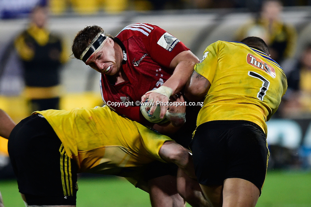 Wyatt Crockett of the Crusaders is tackled by Jack Lam and Ardie Savea of the Hurricanes during the Super Rugby - Hurricanes v  Crusaders rugby match at the Westpac Stadium in Wellington, New Zealand on the 28th of June 2014. Photo: Marty Melville/www.Photosport.co.nz