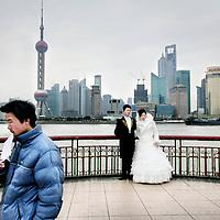China, Shanghai,maart 2008..Bruidstel op de Bund, de koloniale boulevard langs de Huangpu-rivier. De boulevard is in 1992 veranderd in een brede wandelpromenade..Vanaf de Bund ziet u aan de overkant van de Huangpu het nieuwe Pudong verrijzen. Deze wijk moet het hart van de handel en financiën van Shanghai gaan worden. Aan de nieuwbouw wordt dan ook veel zorg besteed en u vindt er veel fraaie voorbeelden van moderne architectuur. Een kenmerkend gebouw in Pudong is de Televisietoren. U kunt er met een snelle lift naar boven en u hebt dan een weids uitzicht over oud en nieuw Shanghai.