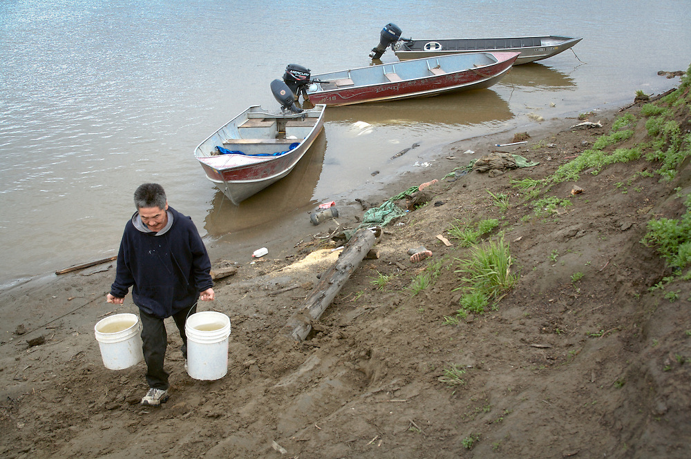 A resident of Kwethluk, Alaska, hauls buckets of river water for household use in this village in the Yukon-Kuskokwim delta where few homes have running water and honeybuckets are common.